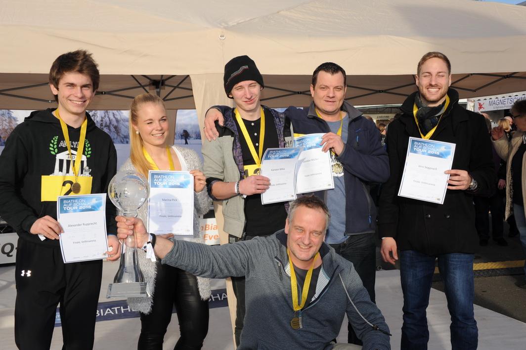 """Wir gratulieren den besten 6 aus insgesamt 1380 Teilnehmern der Biathlon auf Schalke-Tour 2015 und möchten uns herzlich bedanken... ....beim Dorint Hotel & Sportressort Winterberg, für den Siegerpreis, die Reise für 2, die Kai Wilhelmi nun mit Begleitung in dieses Urlaubsparadies am Kahlen Asten unternehmen kann. Auch der herrliche Glas-Wanderpokal, der dem echten Biathlonweltcup-Pokal recht nahe kommt, geht auf eine Initiative des Dorint Hotels & Resort Winterberg zurück. Unser Dank gilt dem Unternehmen CardioFitness, dem Deutschland-Vertrieb für die aus Skandinavien stammenden Thoraxtrainern, die uns heute und künftig Cardio-Biathlon-Duelle ermöglichen, die diese Sportart so authentisch vermitteln, als brächten wir die gespurte Loipe mit.. Und natürlich gilt unser Dank dem FC Schalke 04 Arenamanagement, die allen unseren Etappensiegern nach dem Finale ein einmaliges und unkäufliches Erlebnis bereiteten, indem alle in den """"Gänsehautbereich"""" der Veltinsarena eingeladen waren und den Biathlon auf Schalke abwechselnd aus dem Logenbereich La Ola-Club und aus dem Innenraum der Veltinsarena miterleben konnten. Ein großer Tag braucht viele Wegbereiter!"""